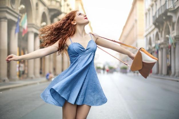 Красивая женщина качается по улице, одетая в милое светло-голубое платье Premium Фотографии