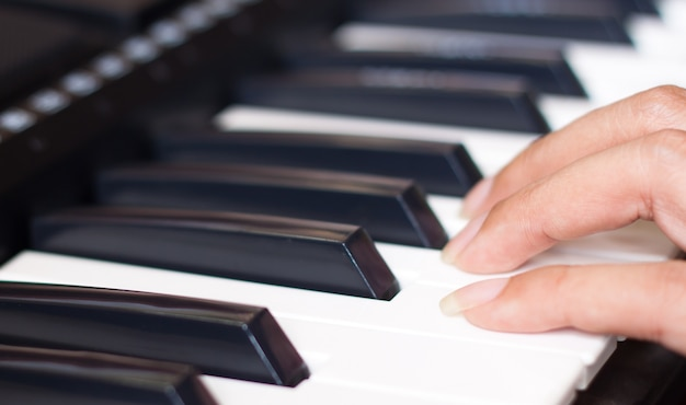 女性の指でピアノのキーボード 無料写真