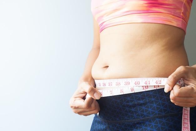 腹部脂肪を持つスリミング女性、腹部脂肪を測定するスポーティーな女性。閉じる Premium写真