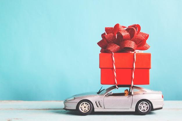 Красная подарочная коробка на автомобильной игрушке с синим пастельным цветом, ретро-эффект фильтра Premium Фотографии