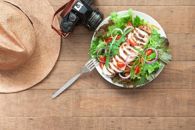 カメラと木製のテーブルの上の帽子とトップビュー健康的なメニュー。幸福とライフスタイルのコンセプト Premium写真