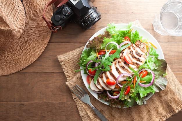 ヘルシーチキンサラダミックスグリーンと帽子とカメラを持つ木製のテーブルの上のトマト。健康 Premium写真