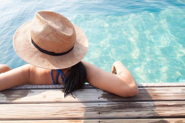 アジアの女性、スイミングプール、旅行休暇の概念でリラックス Premium写真