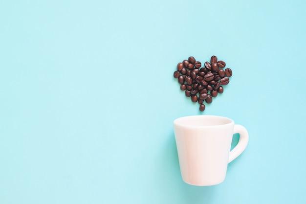 パステルカラーの背景にハート型に配置されたコーヒー豆と白いカップ Premium写真
