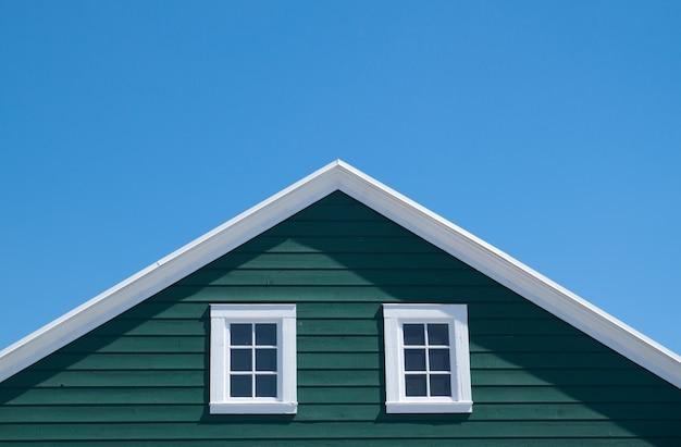 晴れた日に青い空と緑の家と白い屋根 無料写真