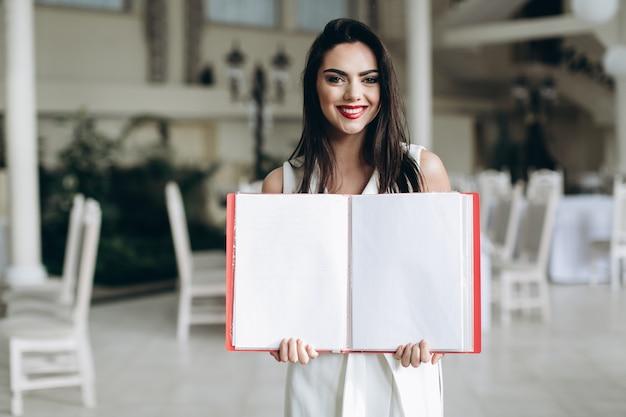 Улыбка женщины, показывая папку меню Premium Фотографии