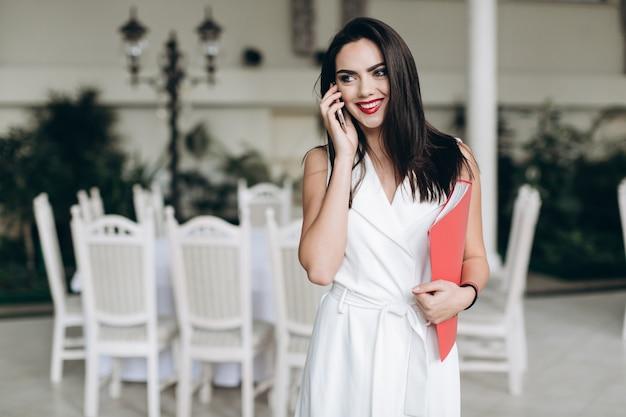 Веселая женщина разговаривает по телефону в ресторане Premium Фотографии