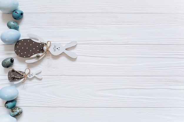イースターウサギ、青い卵、白い木製の背景に雪滴。 Premium写真