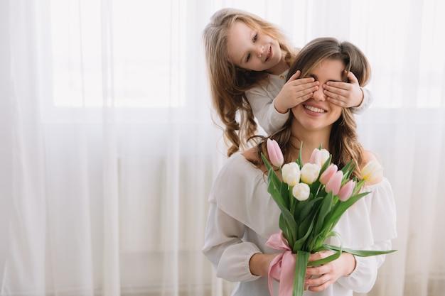 幸せな母の日の概念。子供の娘はお母さんを祝福し、彼女の花チューリップを与えます Premium写真