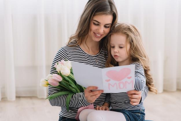 С днем матери. дочь ребенка поздравляет мам и дарит ей открытку и цветы тюльпанов. Premium Фотографии