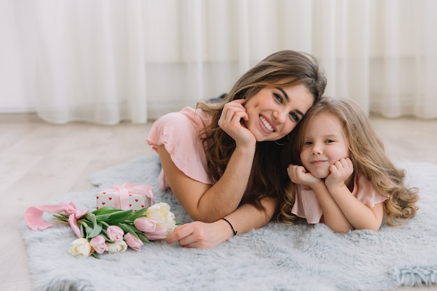 С днем матери. маленькая дочка поздравляет маму и дарит ей цветы тюльпаны и подарок Premium Фотографии
