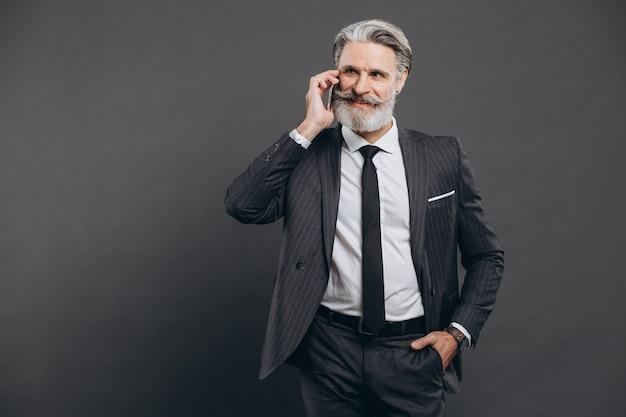 Деловой и модный бородатый зрелый человек в сером костюме разговаривает по телефону и улыбается на серой стене. Premium Фотографии