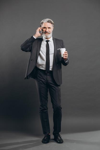 Деловой и модный бородатый зрелый человек в сером костюме разговаривает по телефону, пьет кофе и улыбается на серой стене. Premium Фотографии