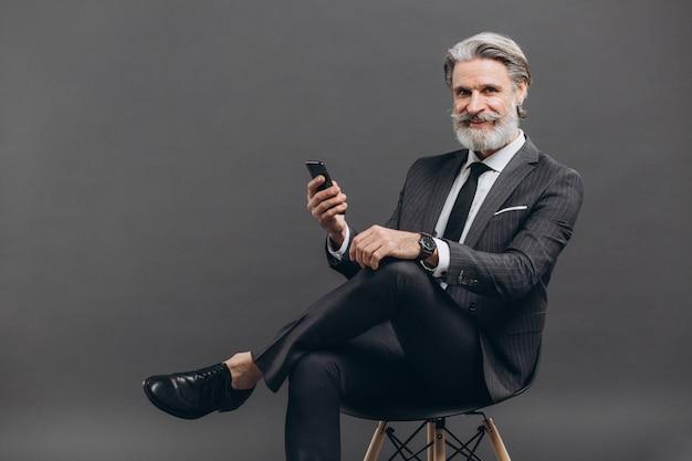 Дело и модный бородатый зрелый человек в сером костюме сидя и используя телефон на серой стене. Premium Фотографии