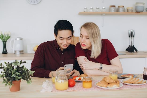 アジア人男性と彼の白人の金髪女性は朝食を持っています。彼らは一緒にキッチンで時間を過ごし、電話でビデオを見ます。 Premium写真