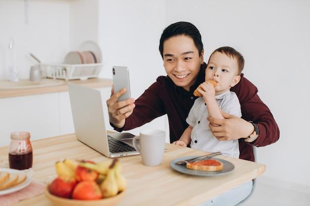 Азиатский папа и его маленький сын завтракают на ноутбуке и принимают селфи на телефоне Premium Фотографии