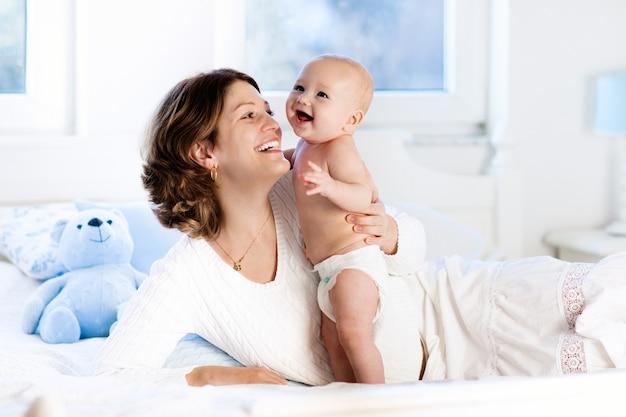 赤ちゃんと母親が自宅のベッドで。ママと子供。 Premium写真