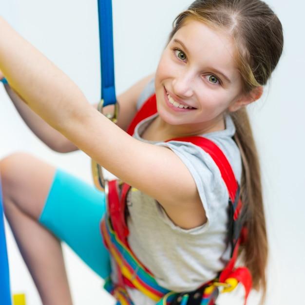 Активная маленькая девочка в ремнях безопасности на стене для скалолазания Premium Фотографии