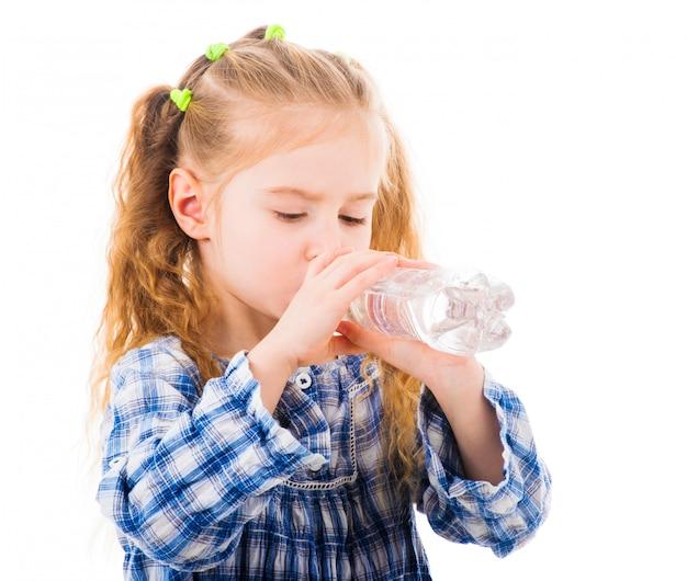 子供の女の子は、ボトルからミネラルウォーターを飲む Premium写真