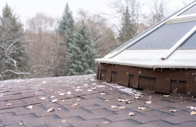 Снег падает на крышу Premium Фотографии
