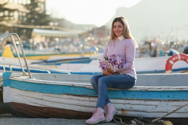 漁船と湾の漁船に座っている女性 Premium写真