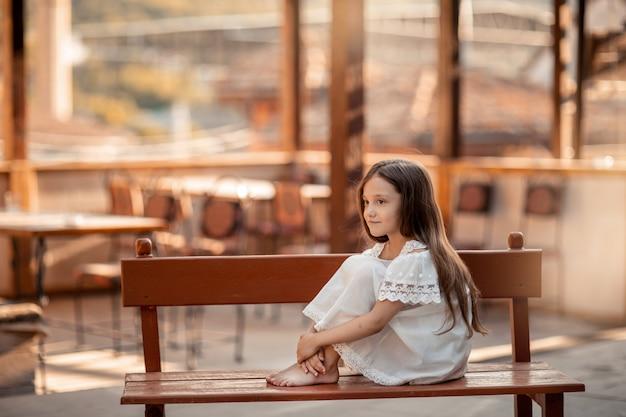 Ребенок с босыми ногами сидит на деревянной скамейке. Premium Фотографии
