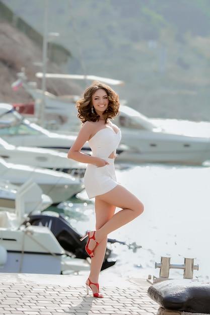 Модель молодой женщины в белом коротком платье гуляет в бухте у моря с яхтами. Premium Фотографии