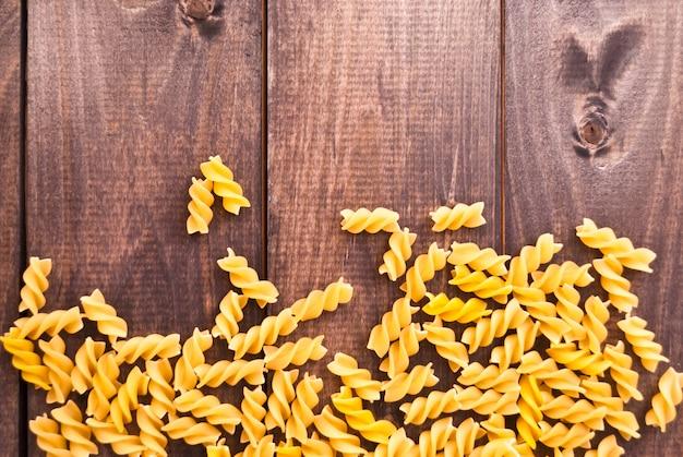Сырые макароны в качестве фона Premium Фотографии