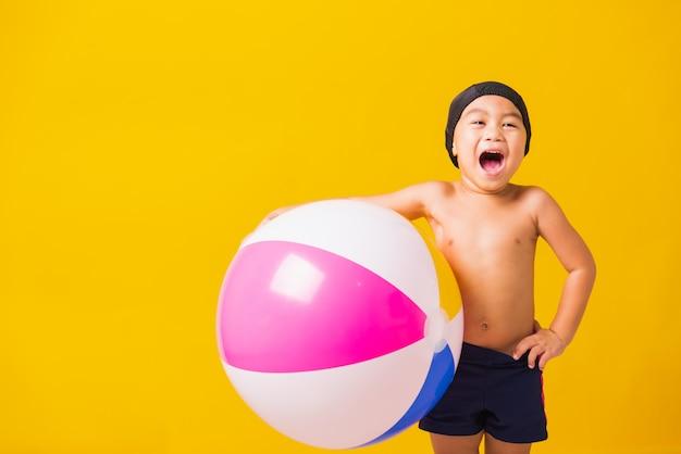 Портрет азиатских счастливый маленький ребенок мальчик улыбается в купальнике держать пляжный мяч Premium Фотографии