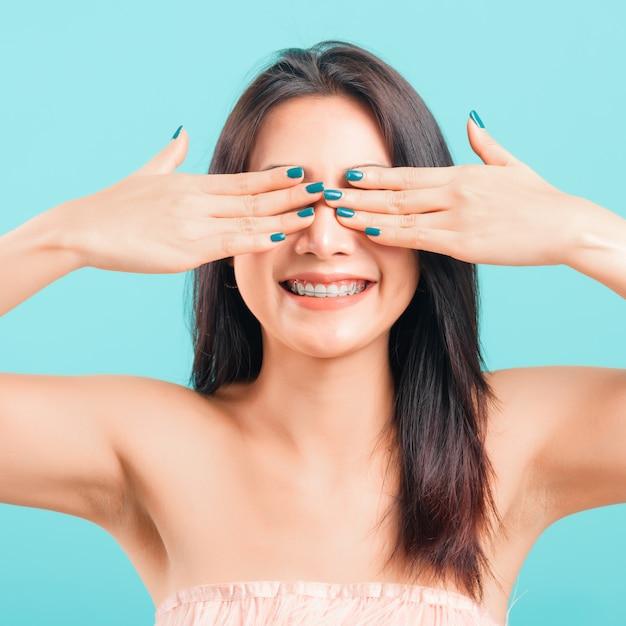 Улыбающееся лицо красивой азиатской женщины прикрывает глаза руками Premium Фотографии