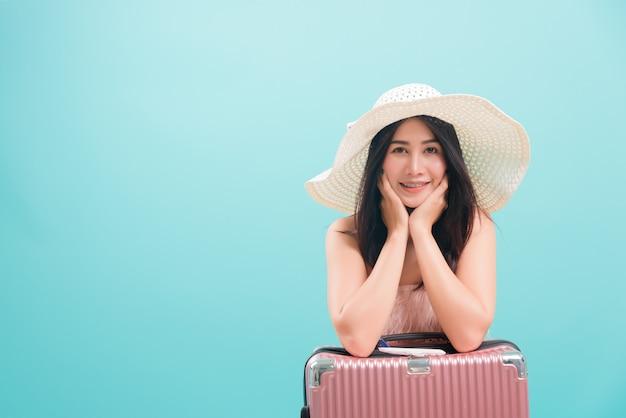 スーツケースバッグに帽子と一緒に旅行する夏の旅行で女性の笑顔 Premium写真