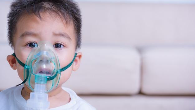 クローズアップアジアの顔コピー子供と蒸気吸入器ネブライザーマスク吸入を使用して小さな子供男の子 Premium写真