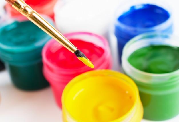 ブラシと色の付いた多くのペイントジャー Premium写真