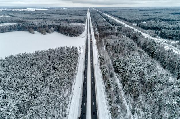 冬の森を通る高速道路。道は地平線に向かいます。 Premium写真