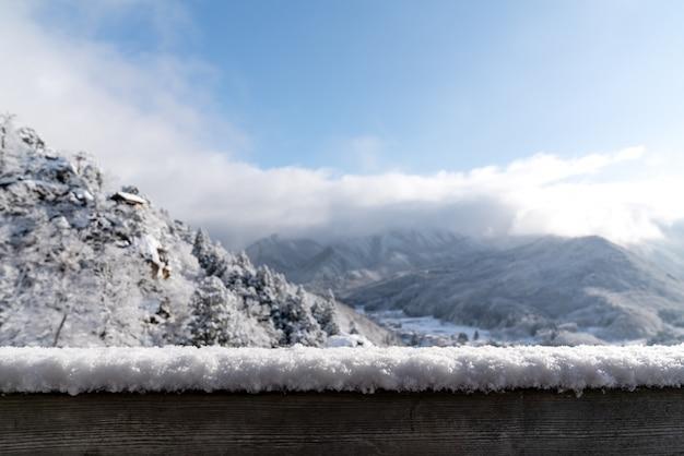 ぼやけている雪の山の景色の前に空の木の板トップテーブル Premium写真