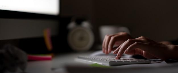 仕事中毒の手のコンピューターで夜遅くまでキーボードを入力 Premium写真
