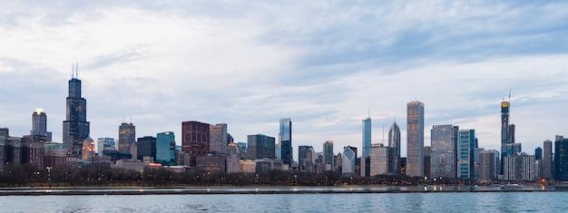 夕方夕暮れの曇りの青い空の夕日のシカゴのスカイラインのビジネス地区の美しい景色。ミシガン湖と都市の海岸線のパノラマビュー。アメリカ、シカゴの有名なアトラクション。 Premium写真
