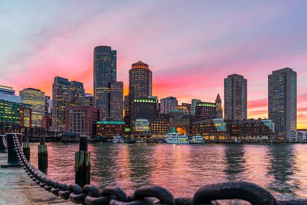 米国マサチューセッツ州ボストンのファンピアパークから幻想的な夕暮れや夕暮れの時間を見たときの日没時のボストンのスカイラインとフォートポイントチャネル。ユナイテッド州のダウンタウンの美しいカラフルなスカイライン。 Premium写真