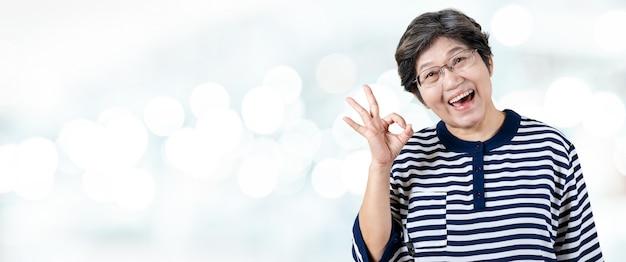 幸せな上級アジアの女性のジェスチャーや手を見せて肖像画の大丈夫 Premium写真