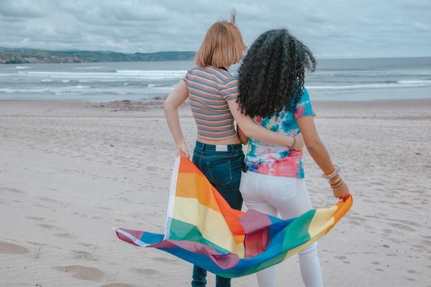 ロマンチックな夕日を見ながら砂浜でゲイプライドフラグを移動する若いレズビアンカップル-画像 Premium写真
