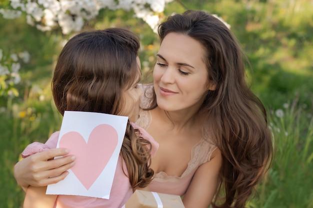 母の日おめでとう!子娘はお母さんにハートのカードとプレゼントを差し上げます。 Premium写真