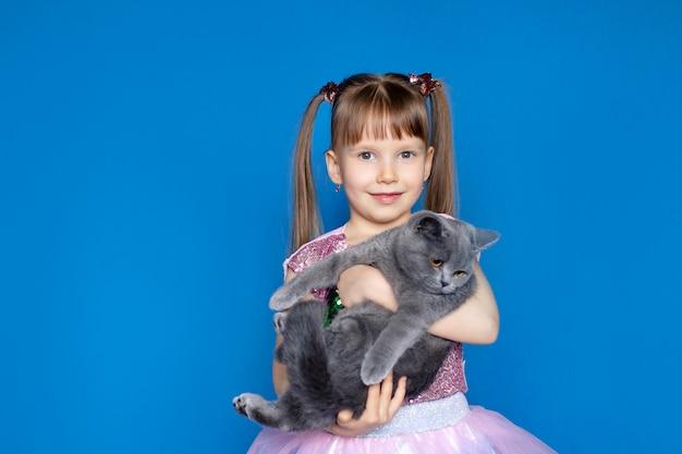 Милая девушка держит в руках серый шотландский котенок. Premium Фотографии
