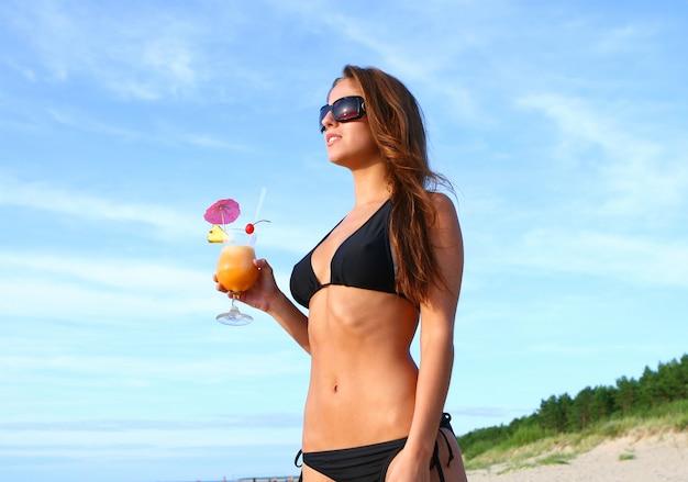 Женщина в бикини на пляже со свежим летним коктейлем Бесплатные Фотографии