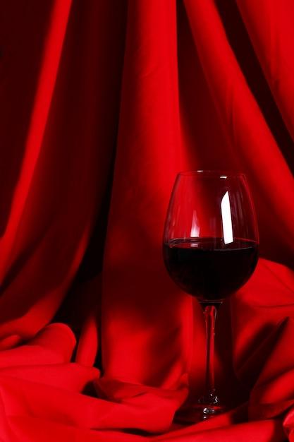 Стакан красного вина на красной ткани Бесплатные Фотографии