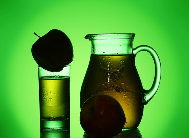 緑のスポットライトで新鮮で冷たいリンゴジュース 無料写真