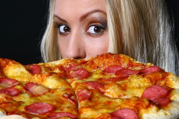 Красивая молодая женщина ест пиццу Бесплатные Фотографии