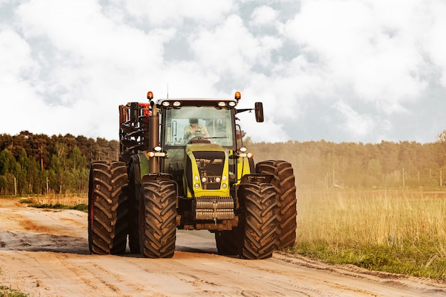 牧草地の近くの田舎で道路上のトラクター 無料写真
