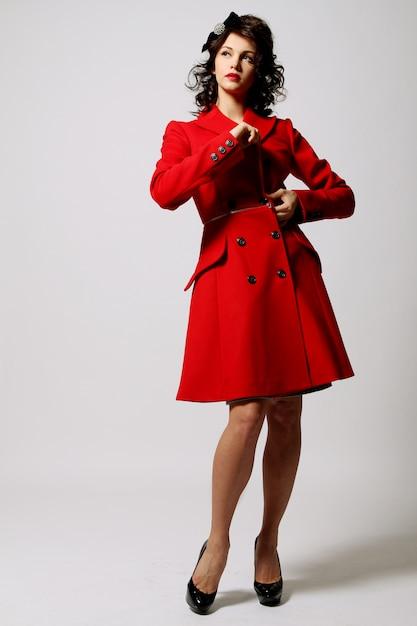 Красивая молодая женщина в красном пальто Бесплатные Фотографии