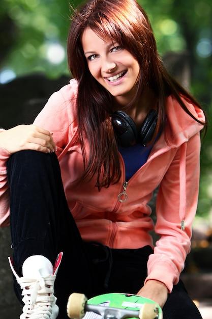 Красивая девушка подросток с наушниками в парке Бесплатные Фотографии