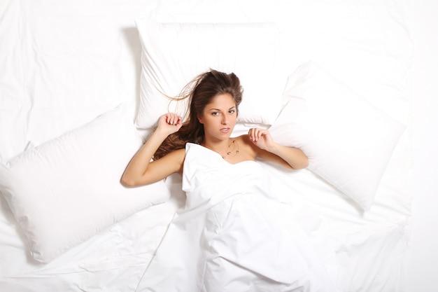 Молодая женщина, отдыхая в постели на утро Бесплатные Фотографии